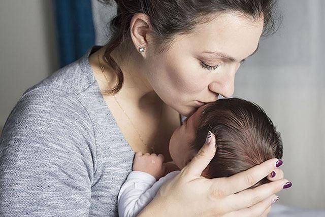 mama ljubi novorođenče u čelo